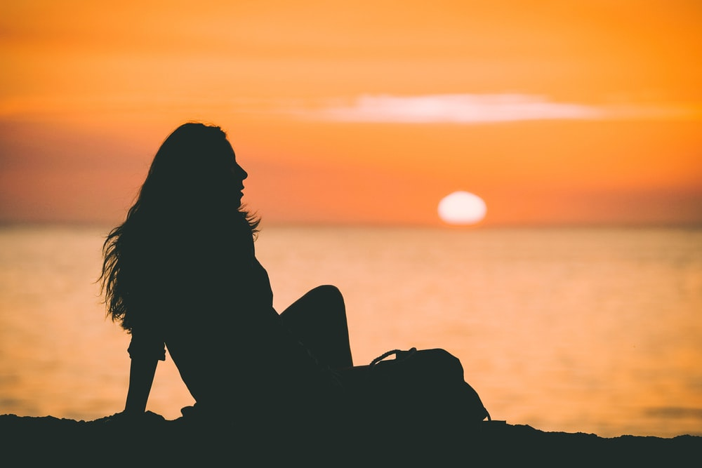 silhouette photo of woman at sunset
