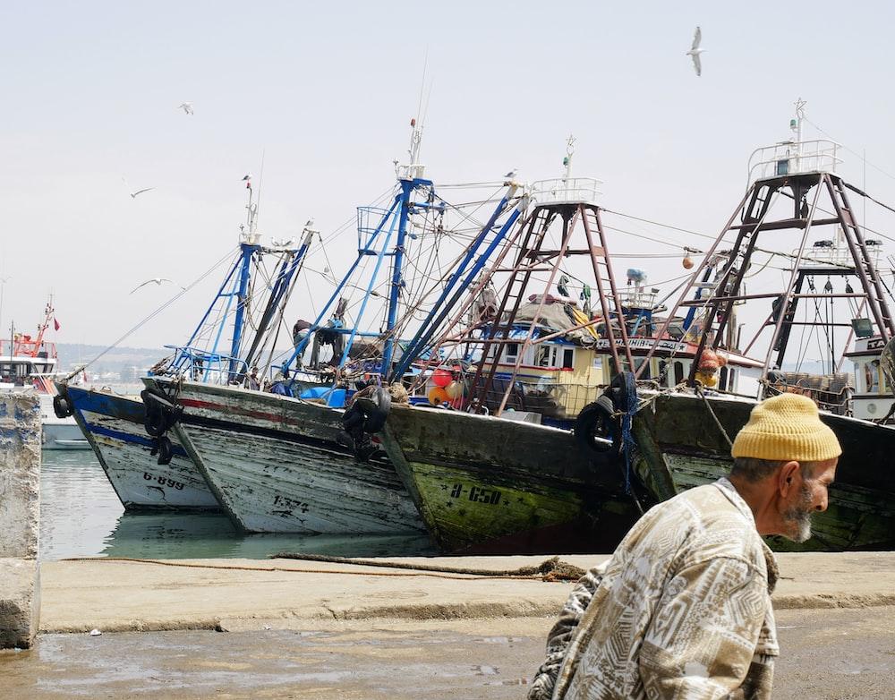 man walking near boat ships during daytime