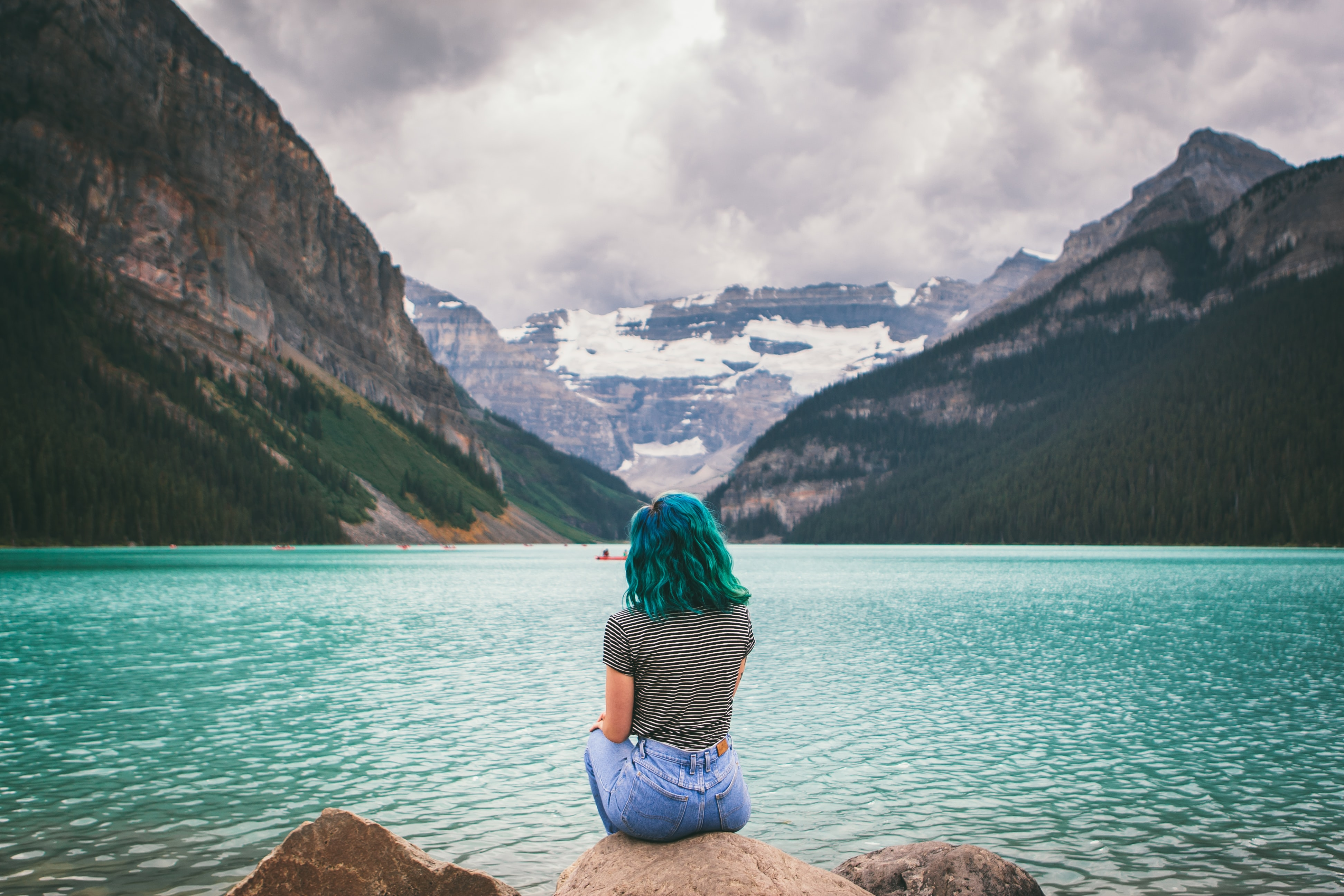 woman sitting on chair near body of water
