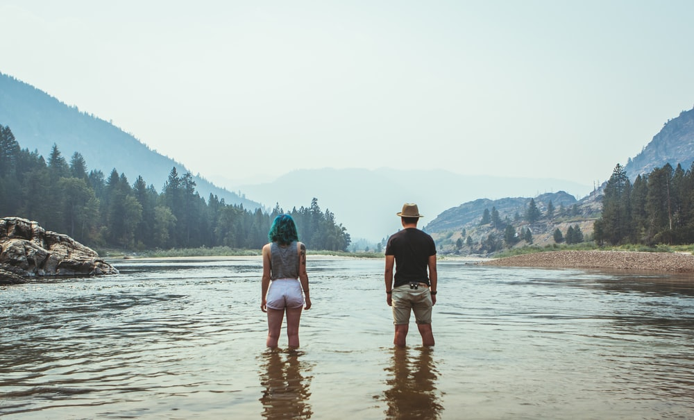 man and woman standing on river