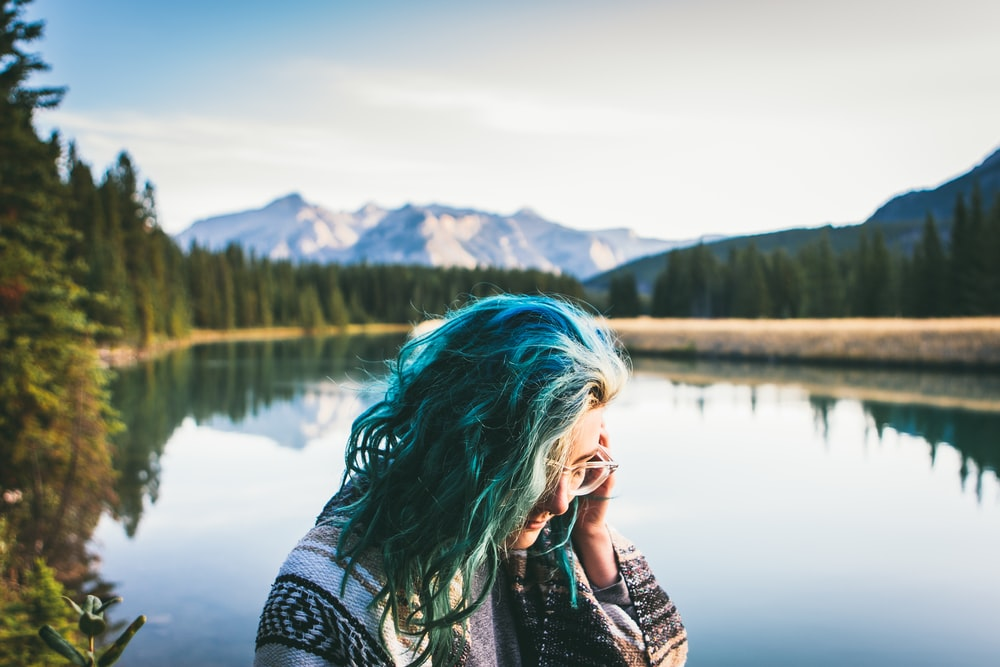 blue haired woman in grey top in front of body of water