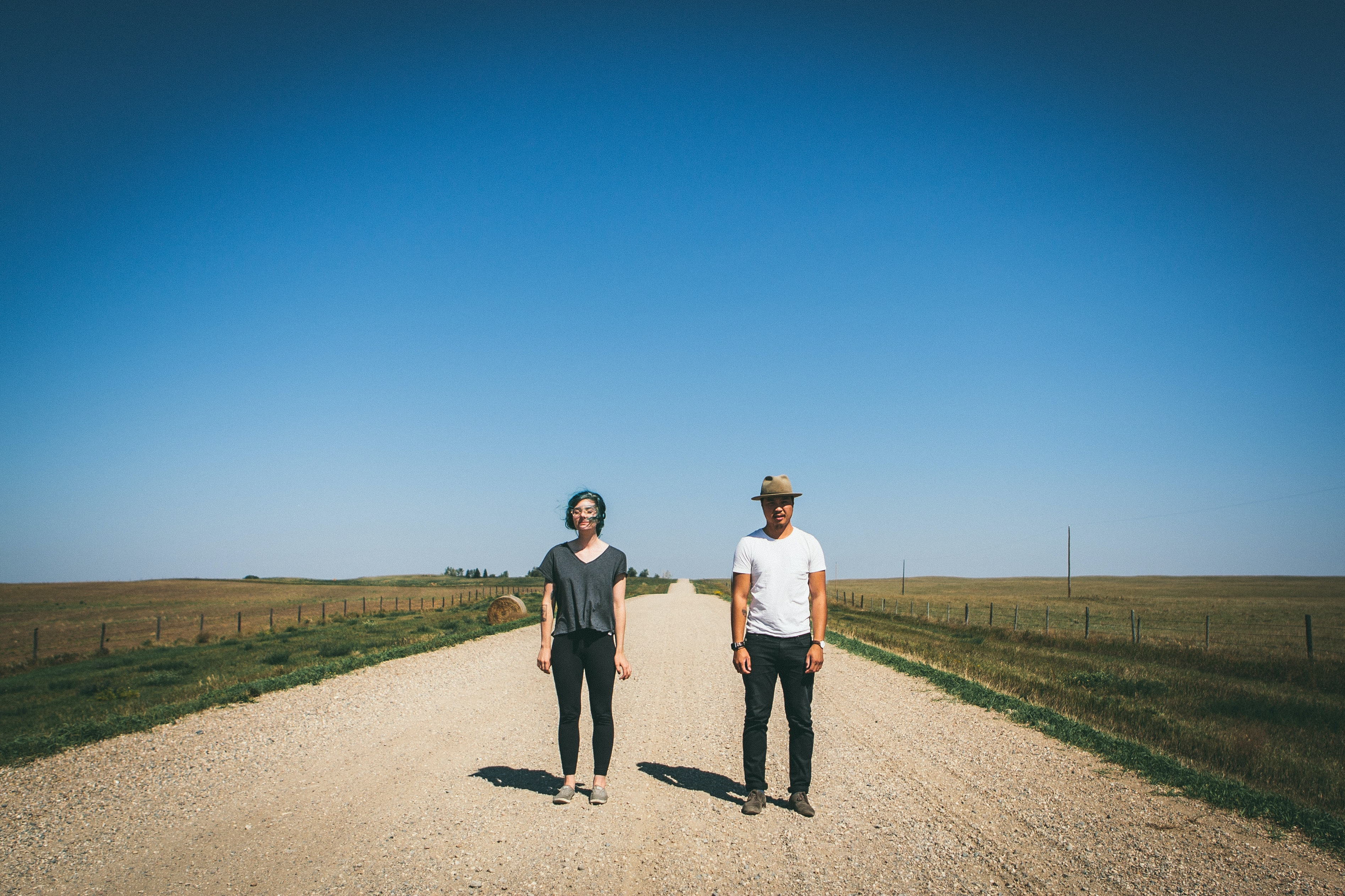 man and woman standing on road between grass fields during daytime