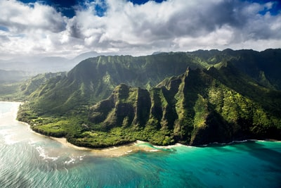 aerial photography of green mountain beside body of water under white sky hawaii zoom background