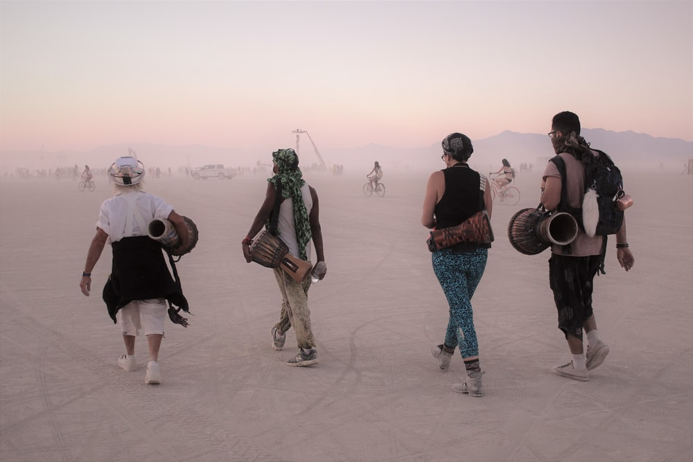 four person walking while carrying drums