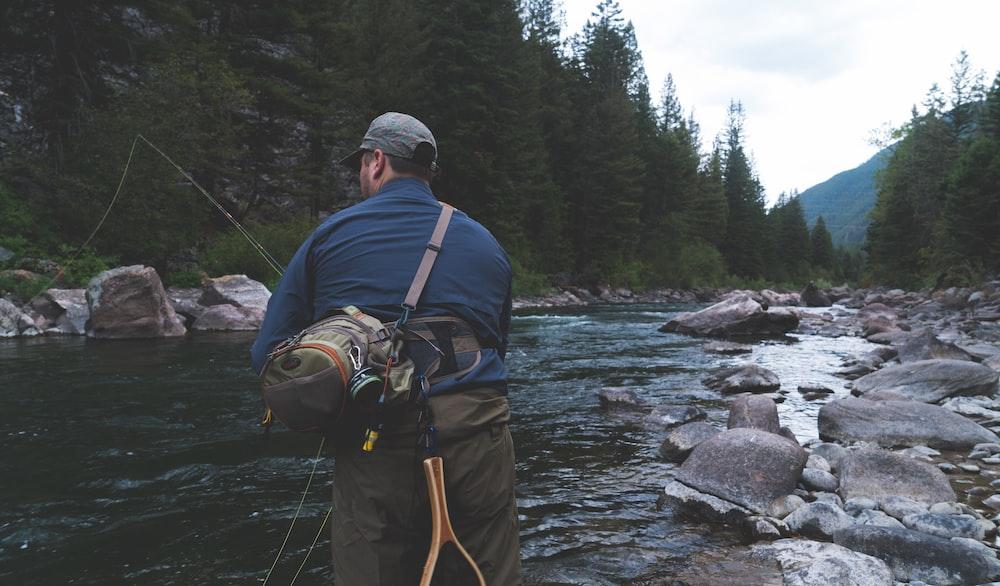 man fishing on river at daytime