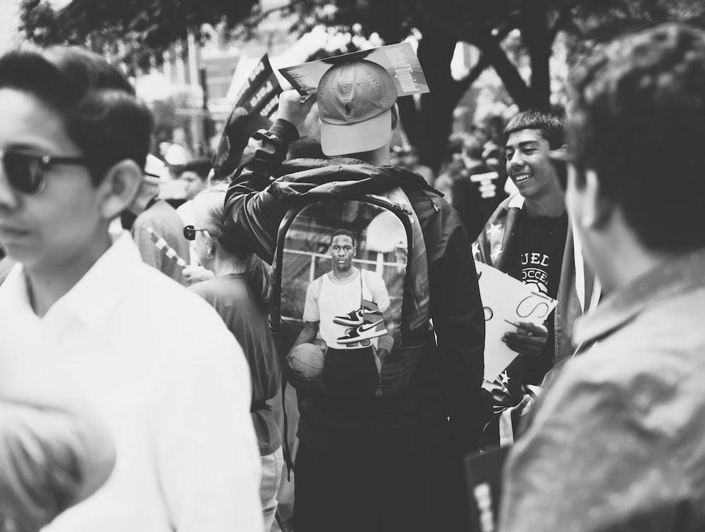 man wearing backpack near people