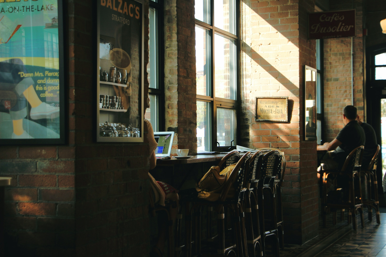 three person sitting near bar stall