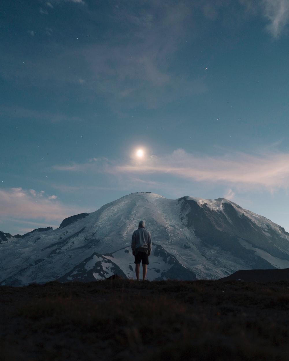 man standing on grass field overlooking mountain