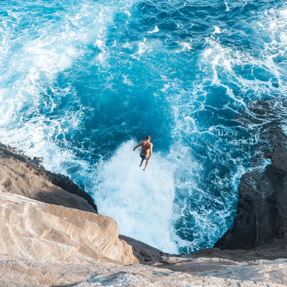 aerial photo of man jumping on cliff to the water