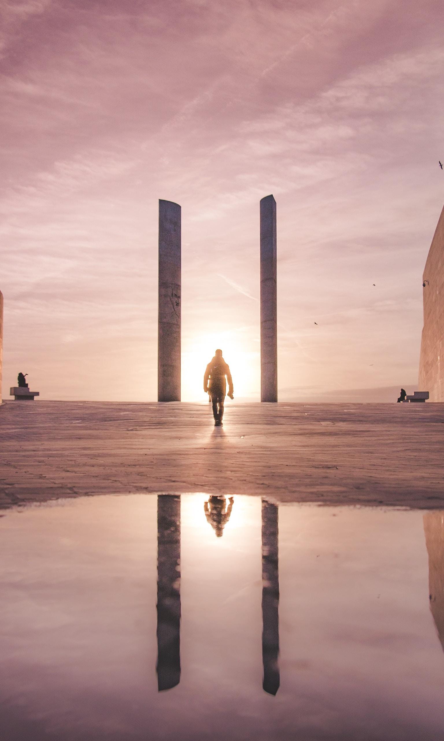 man walking towards the sun