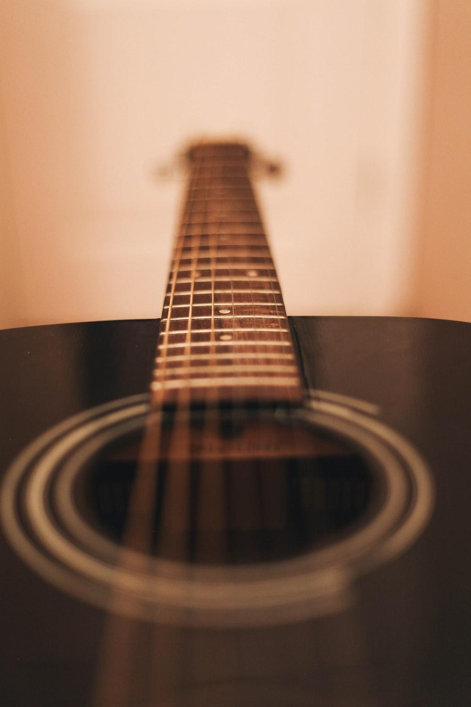 close-up photograph of black dreadnought acoustic guitar