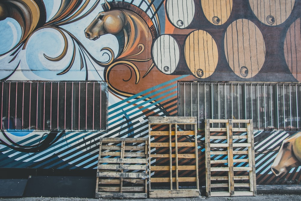 three brown wood pallets leaning on wall