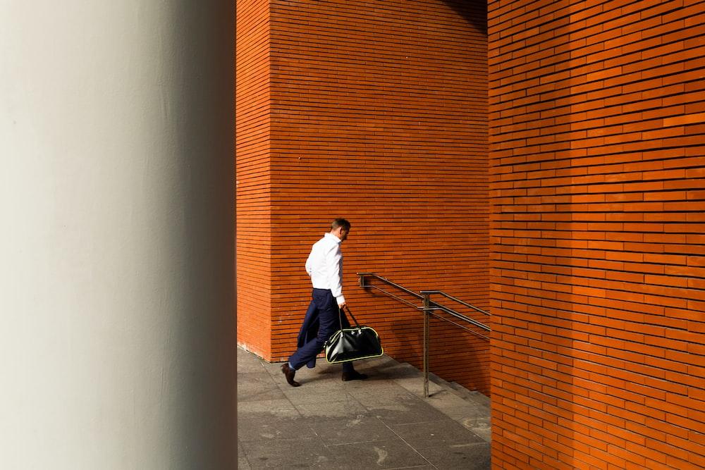 man holding duffel bag down stair