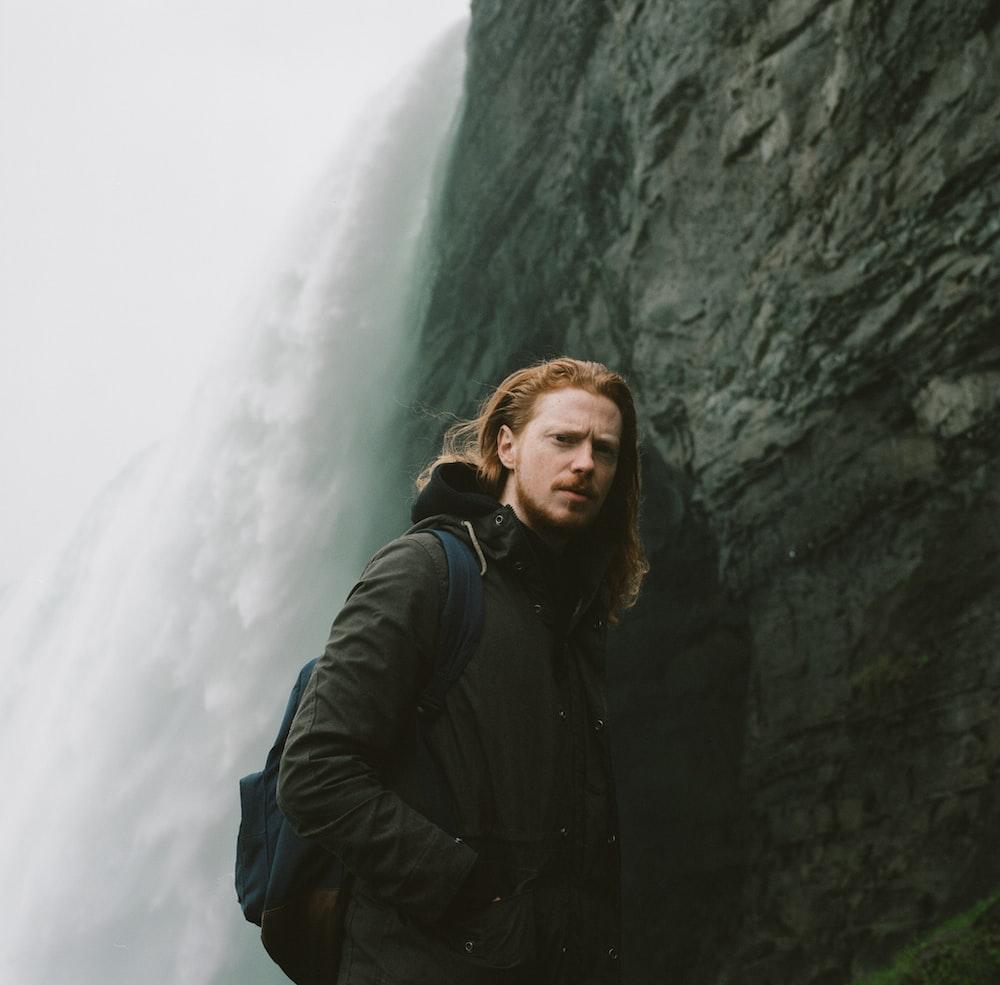 man in black jacket standing beside rock formation