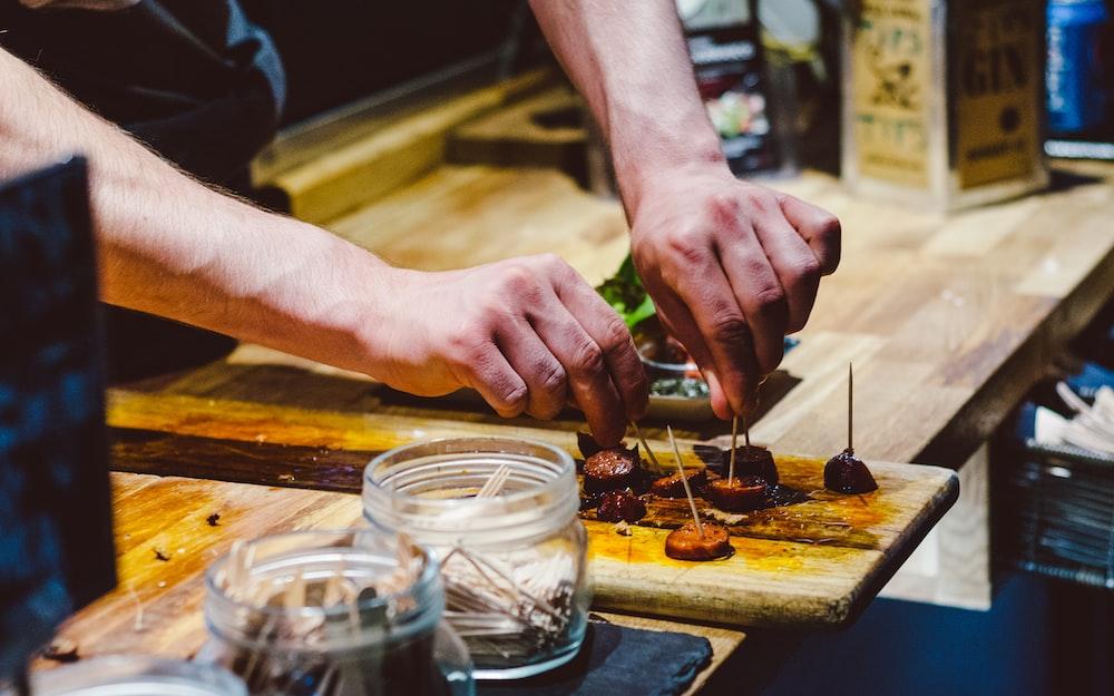 person preparing bite-sized sausage on board