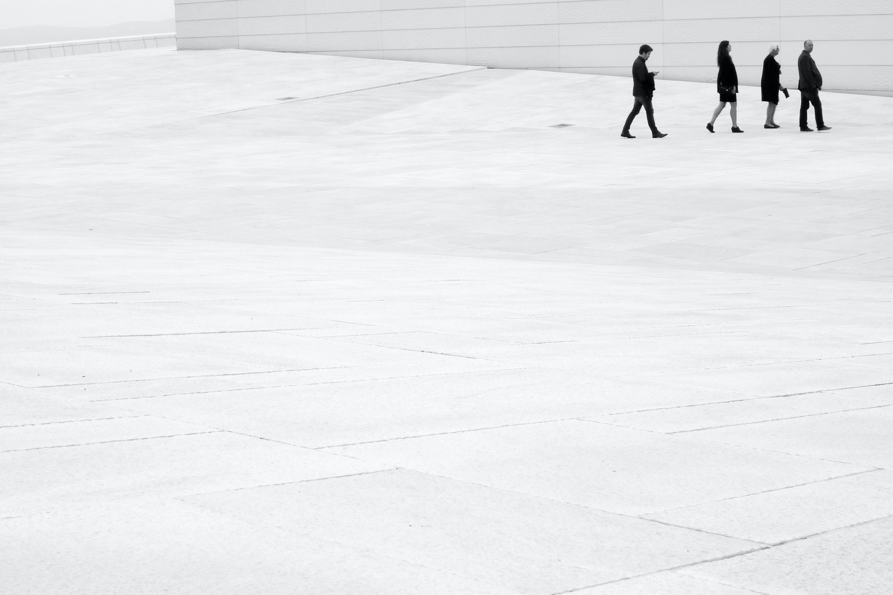 four people walking near wall
