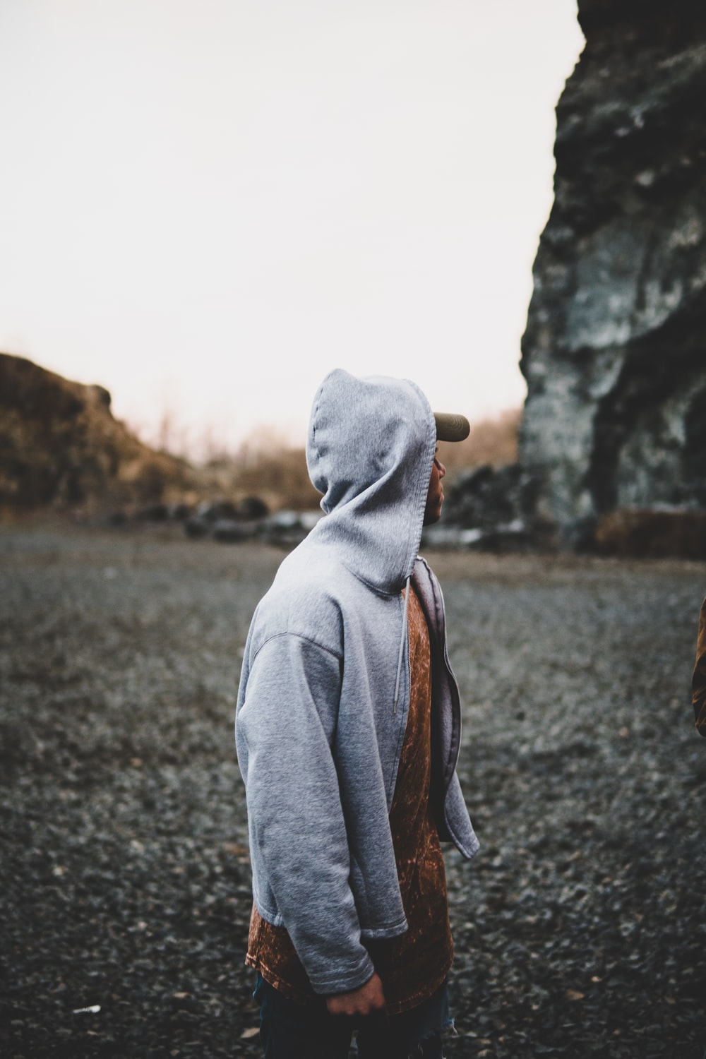 selective focus photography of man standing near rock formation