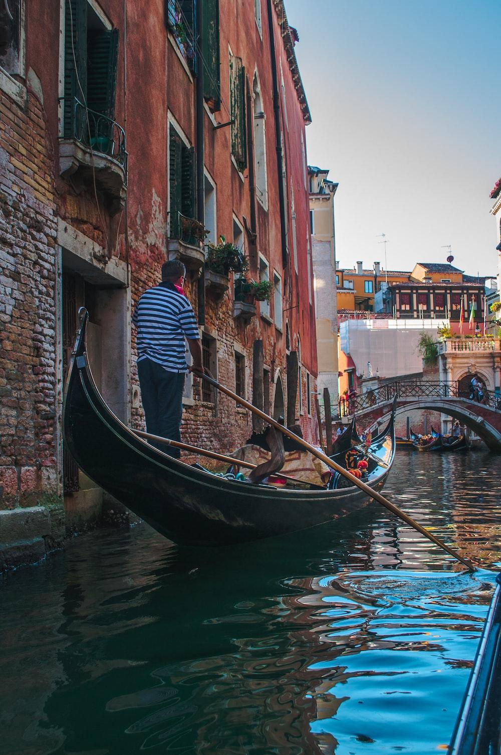 man riding boat at Venice Canal