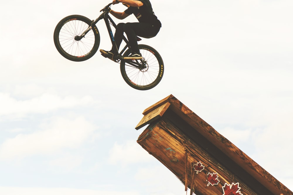 man riding on BMX bike on mid air during daytime