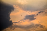 plane flying under clouds