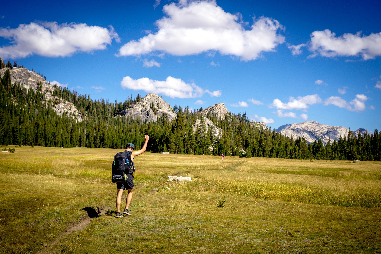 man walking on grass field during daytime