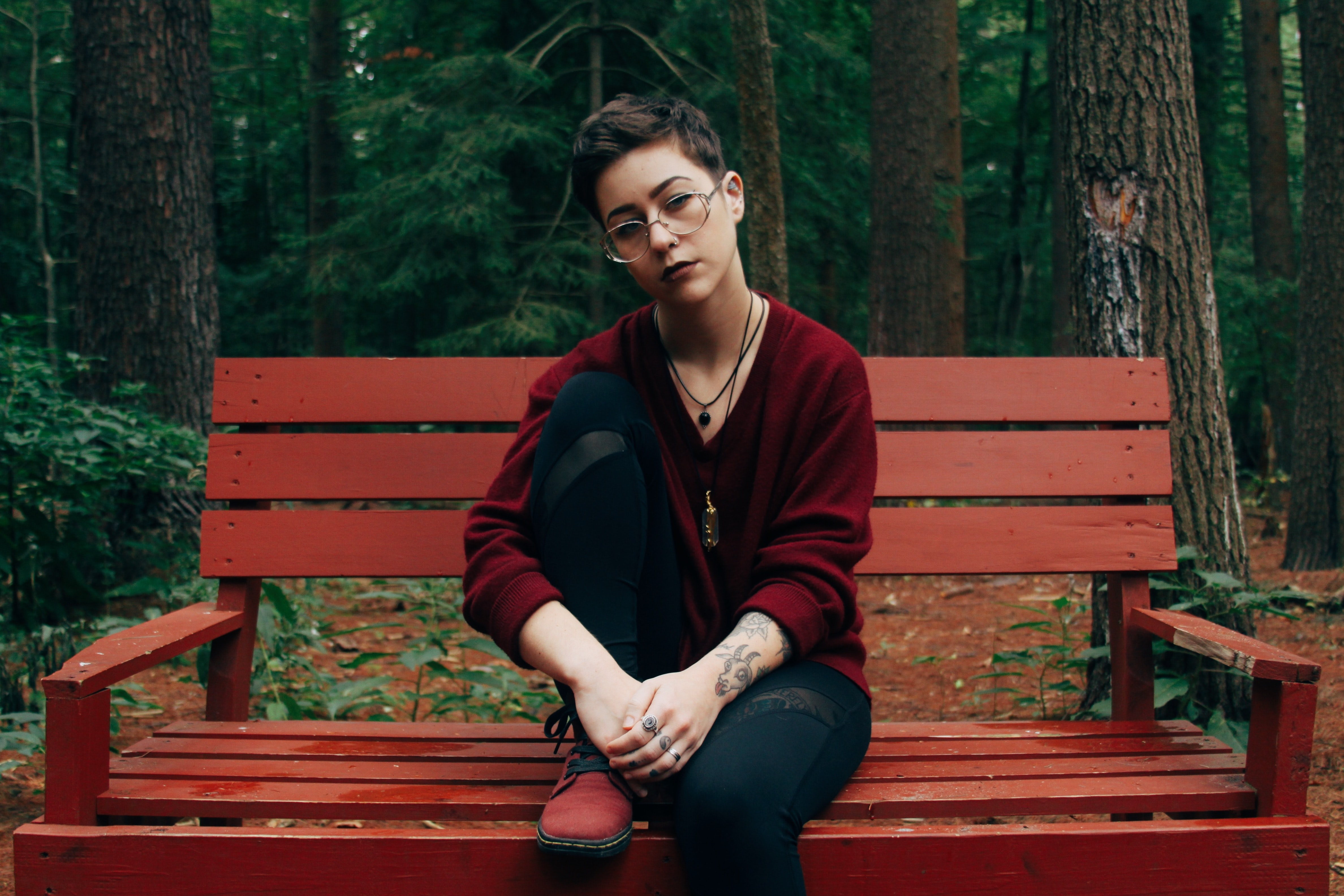 woman sitting on bench near forest