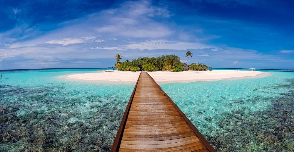 brown dock on body of water under blue sky