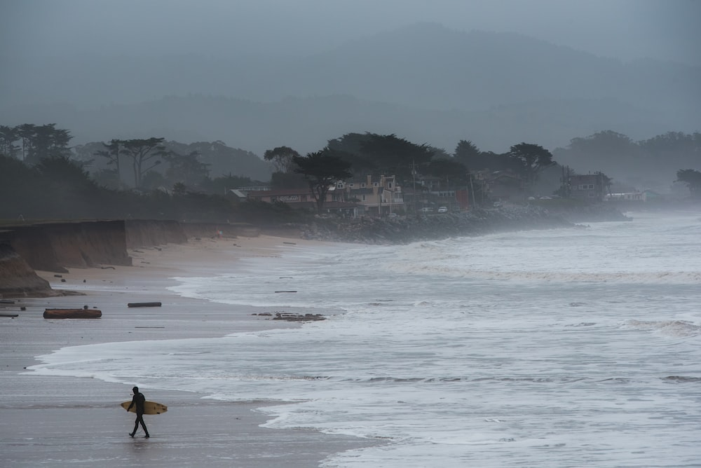 person walking and carrying surfboard on seashore during foggy weather