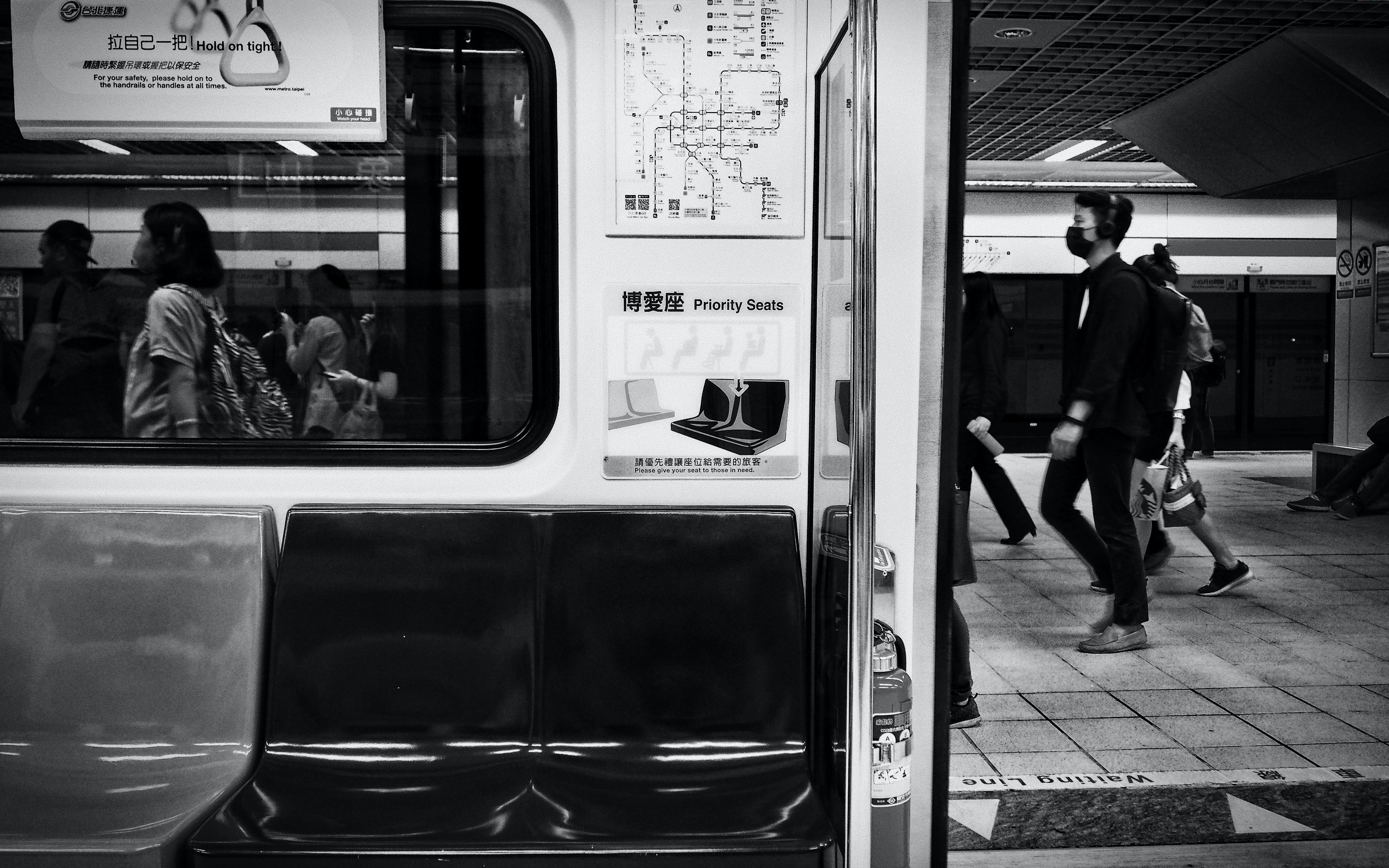 grayscale photography of man walking through the train