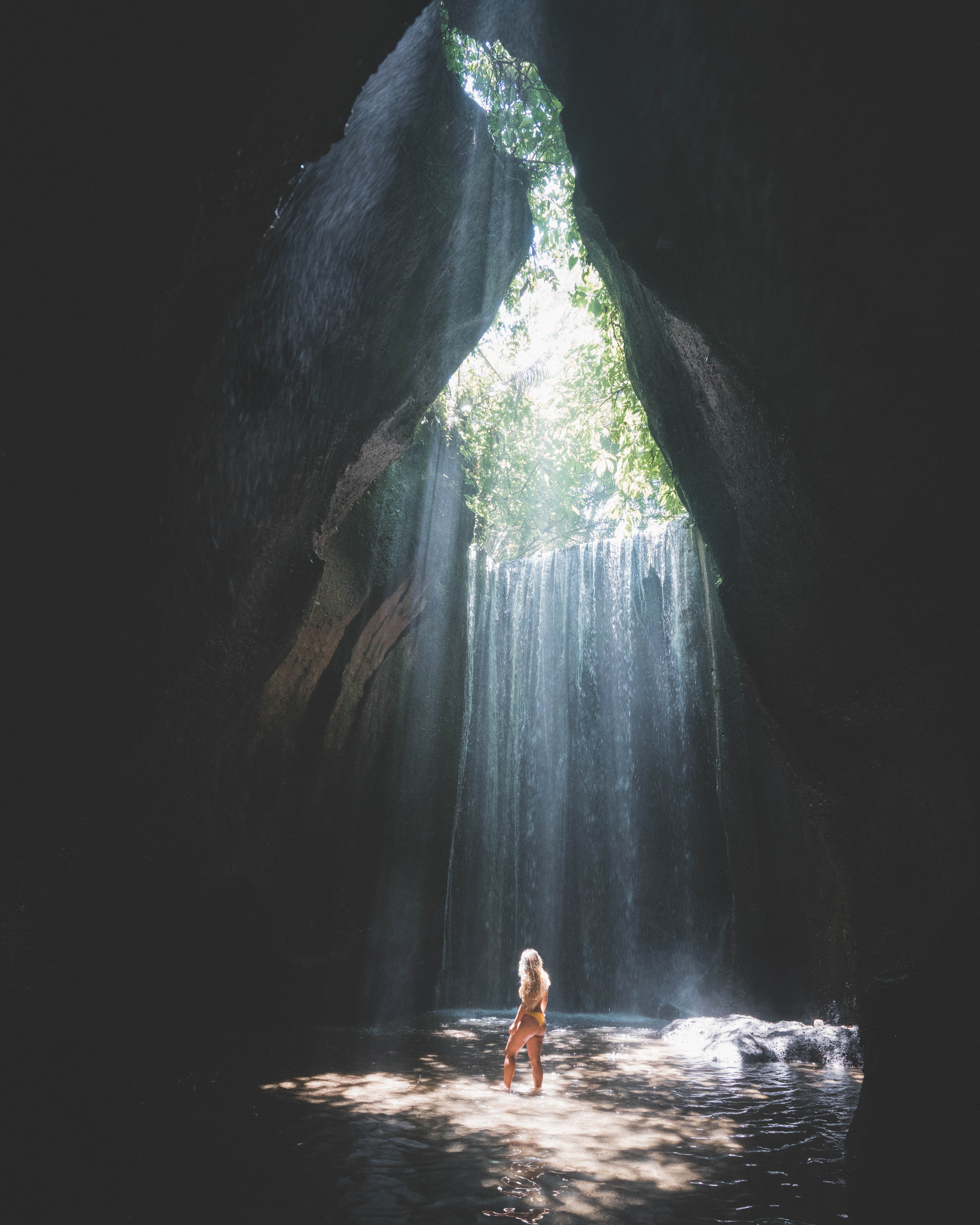 woman standing under cave hole