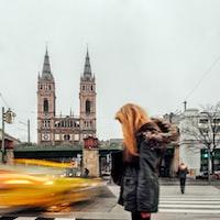 blonde woman wearing winter coat standing on roadside timelapse photography