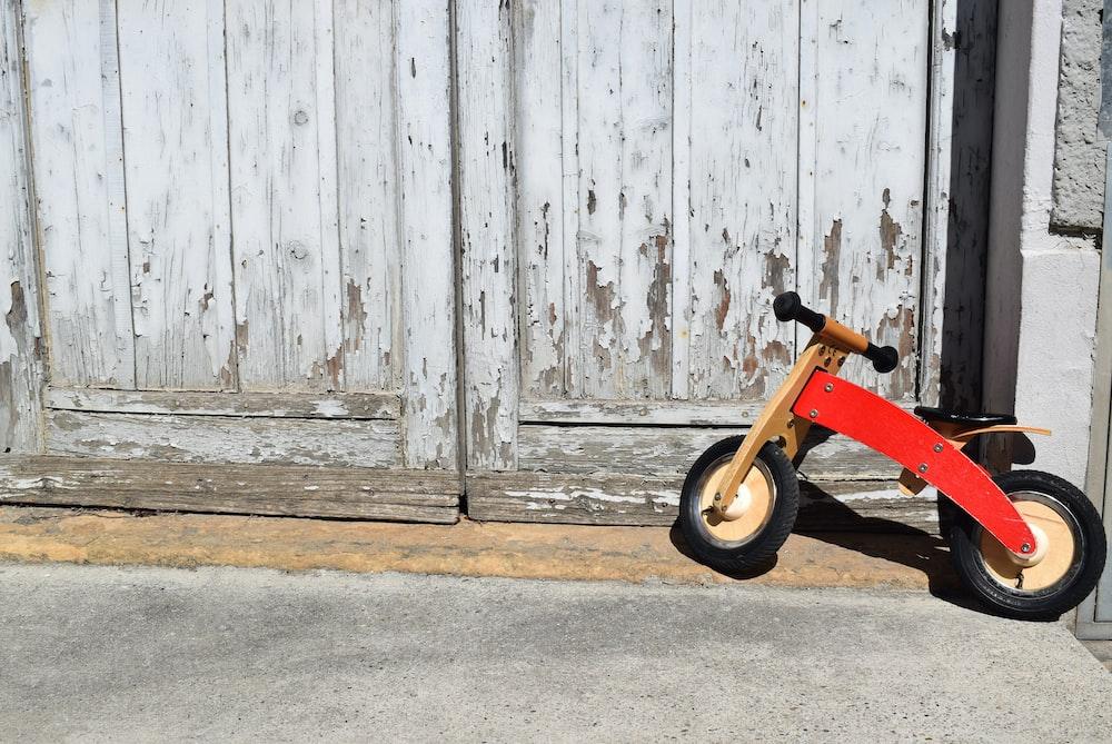toddler's orange bicycle park beside door