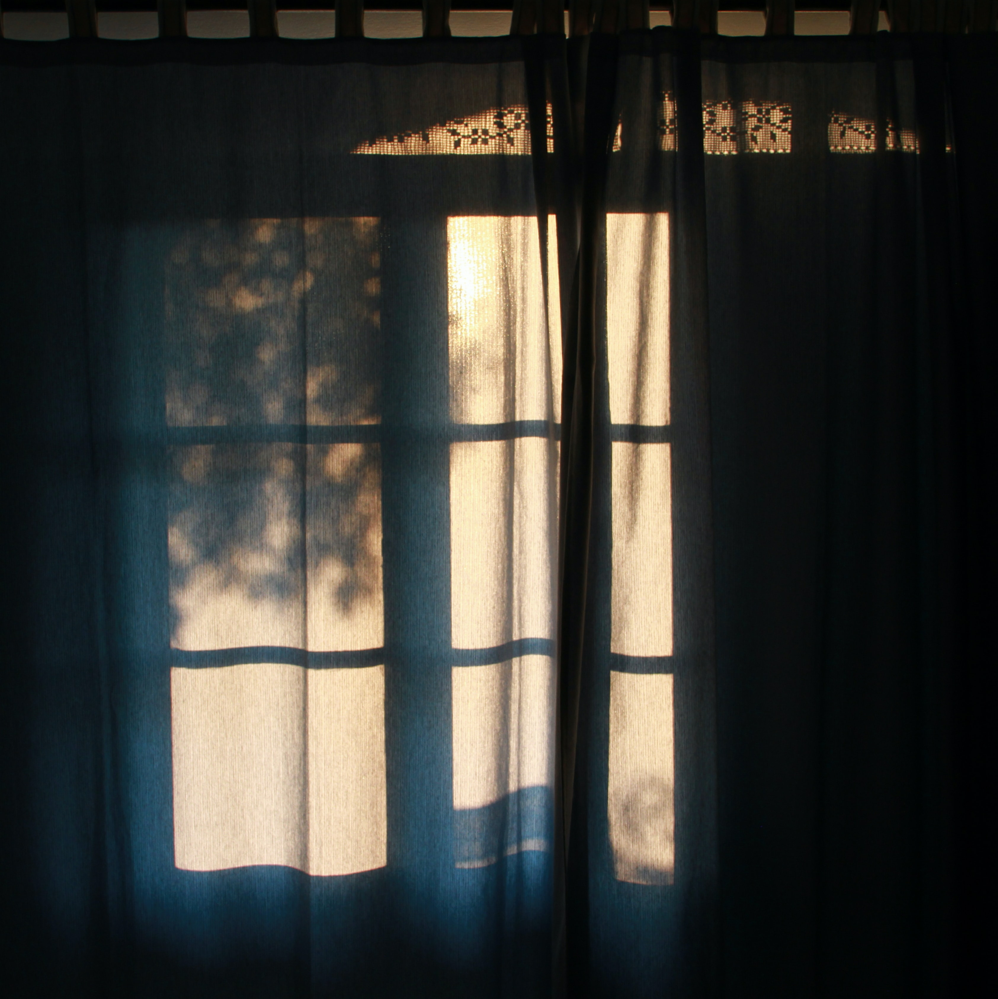 blue curtain in front of window during daytime