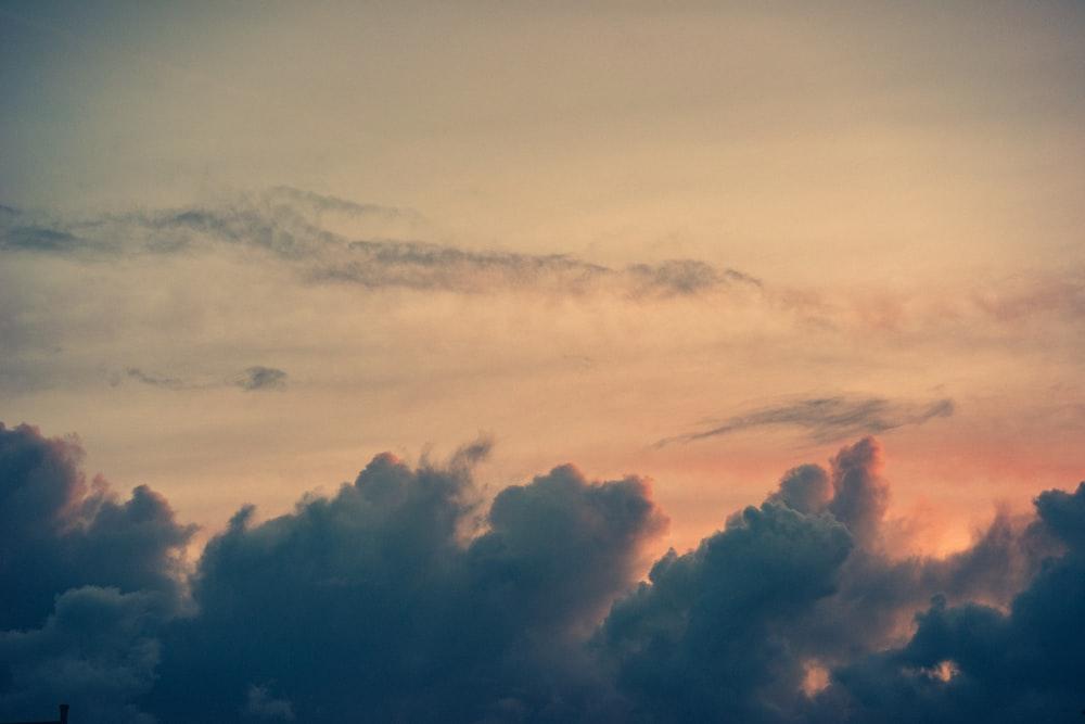 photo of dark clouds in a peach colored sky