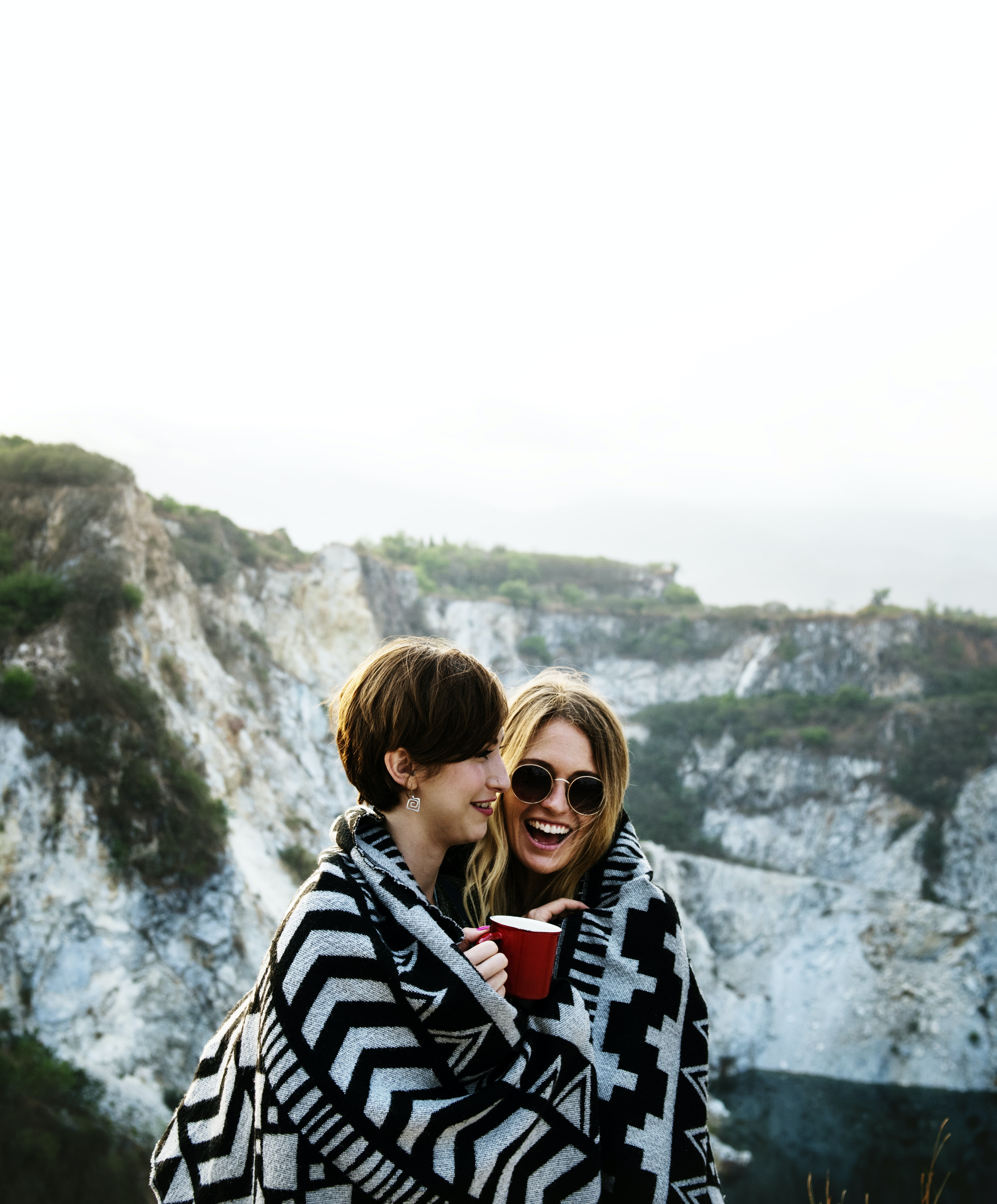 two woman covered by blanket holding cup of coffee near the mountain