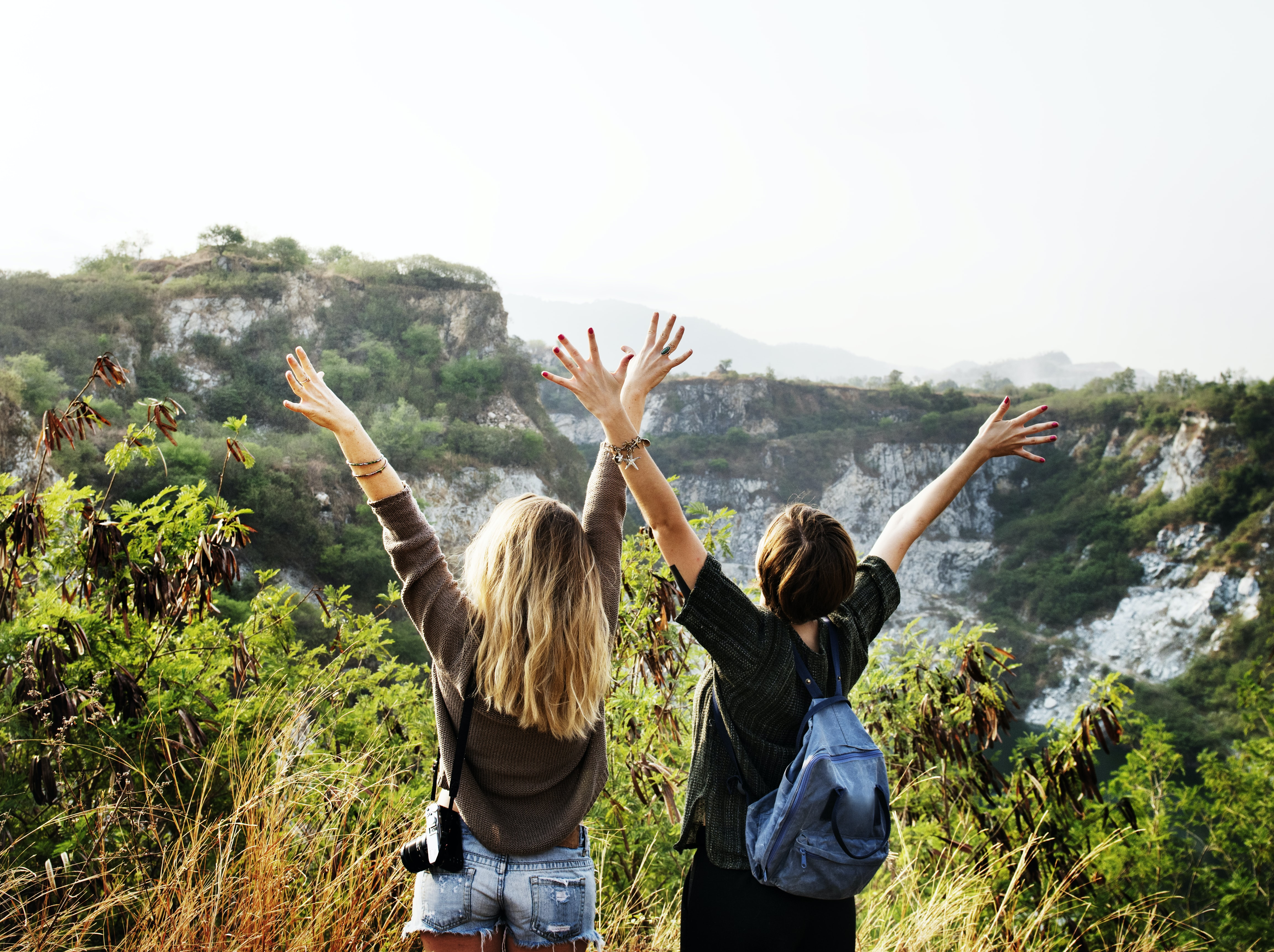 two person raising their hands facing mountain