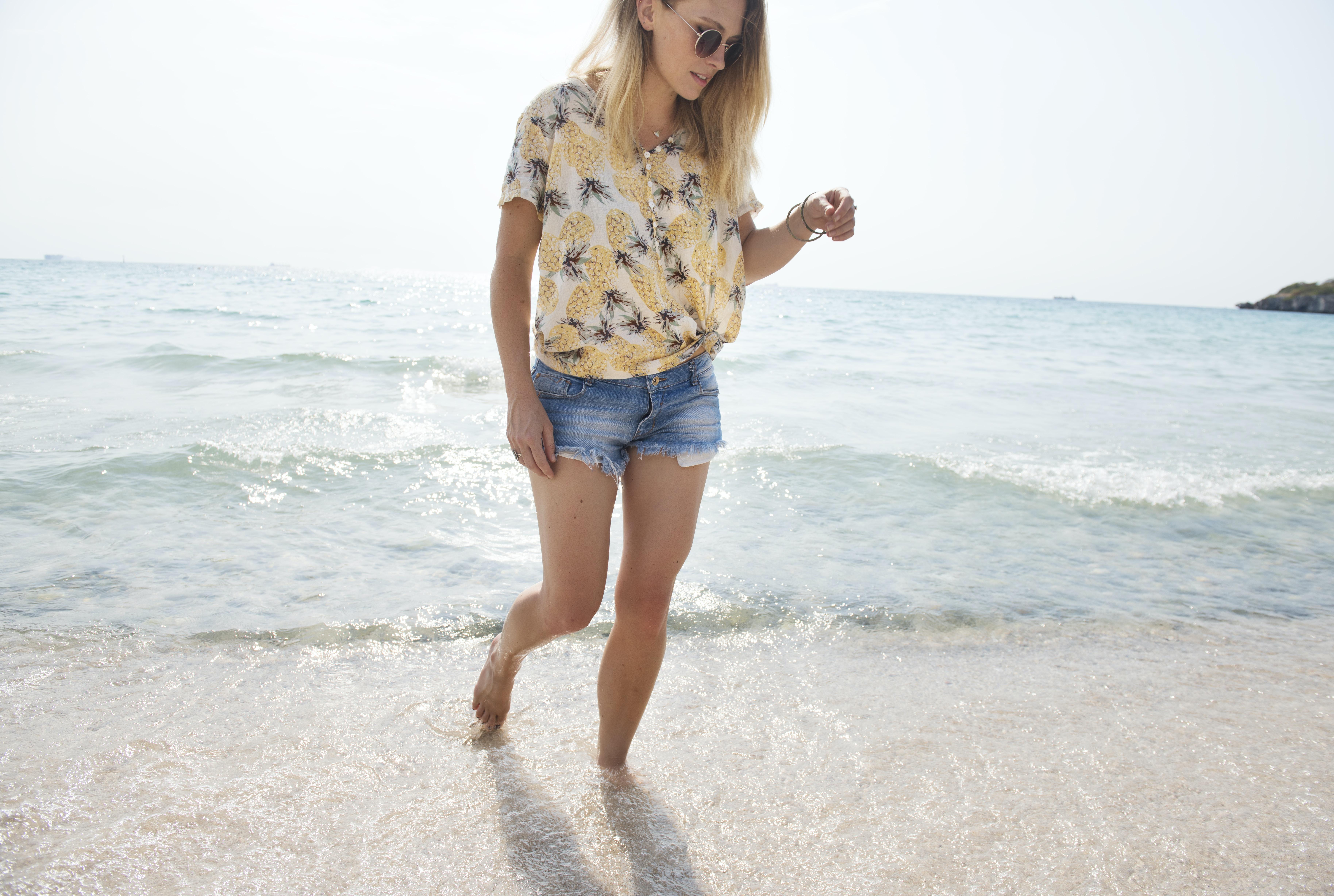 woman walking on seashore with sea waves