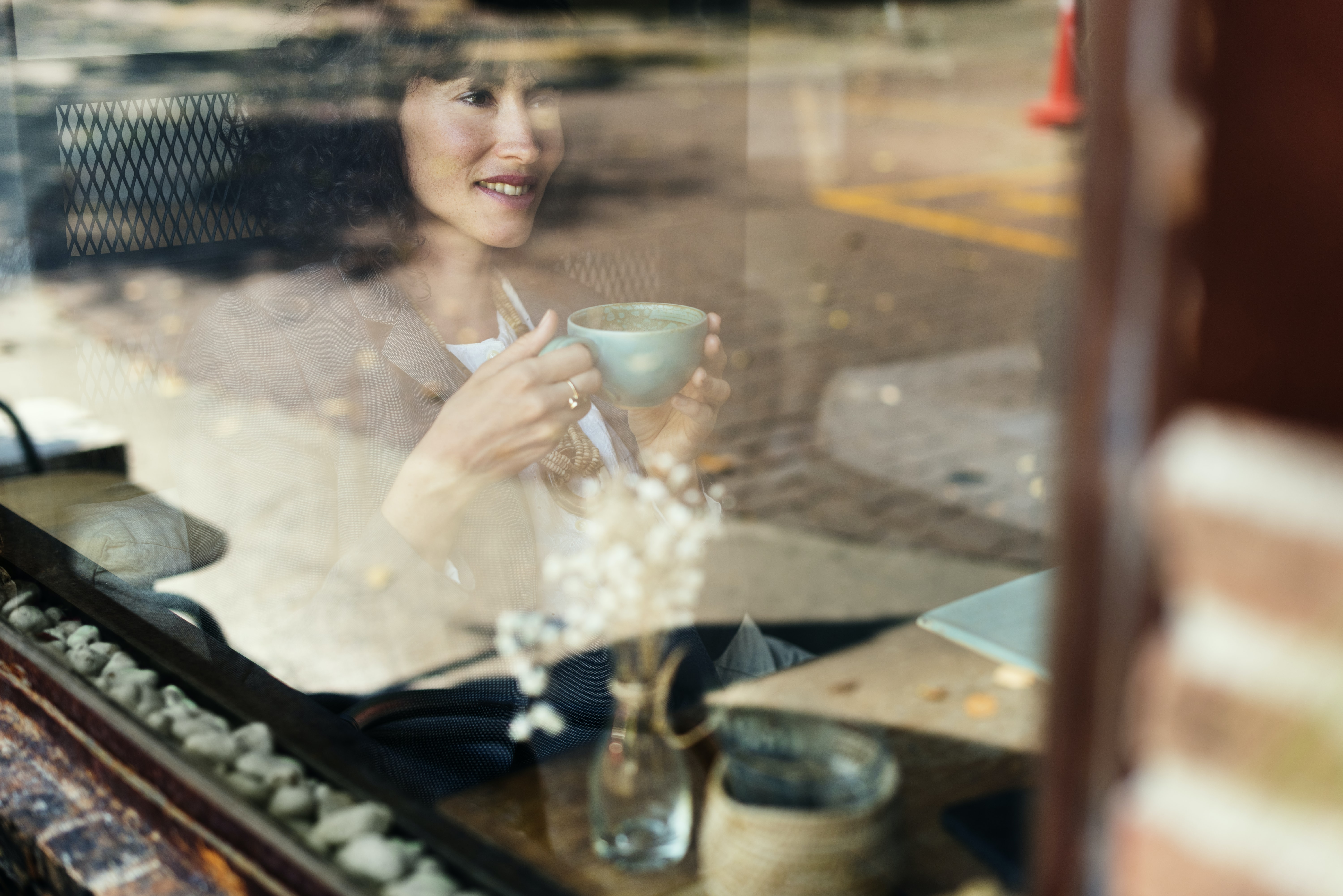 woman sitting inside train holding teacup