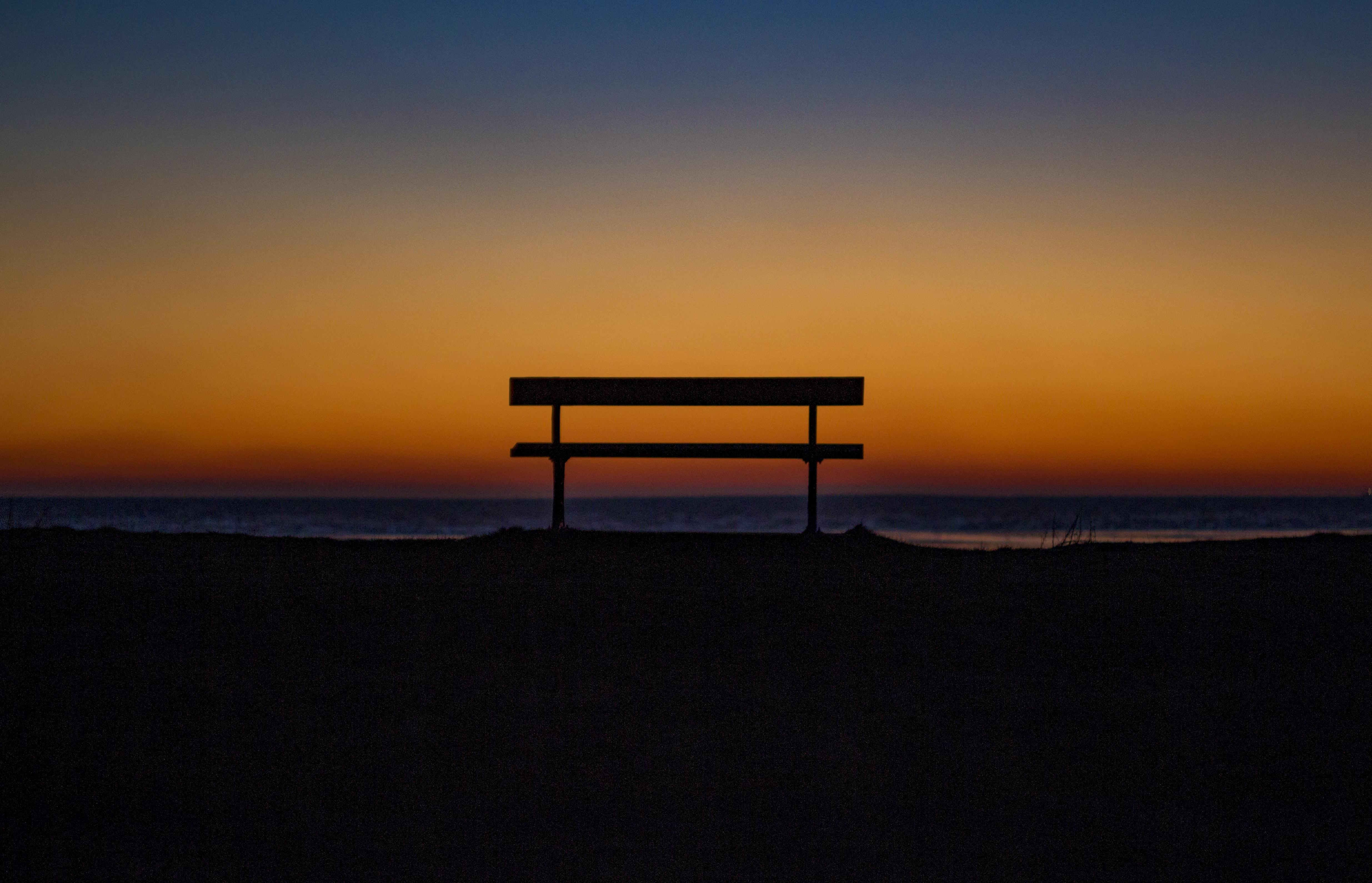 bench near shoreline during sunset