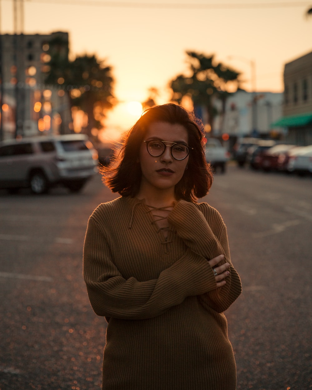 woman standing on road near vehicles during golden hour