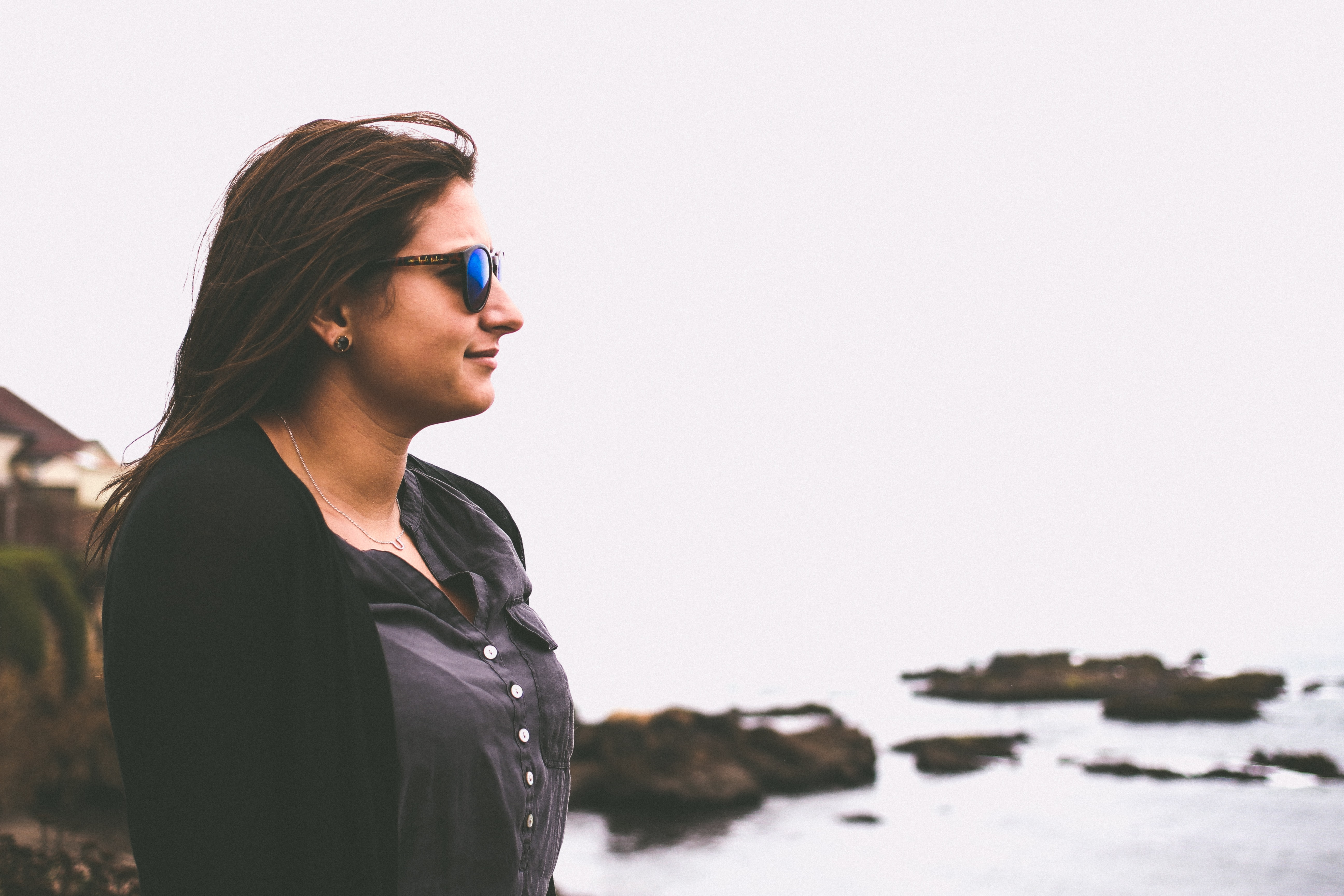 woman in black cardigan standing in front of beach during daytime