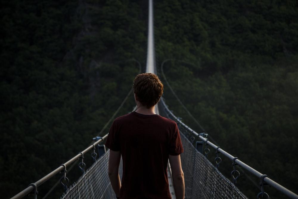 man standing alone on hanging bridge