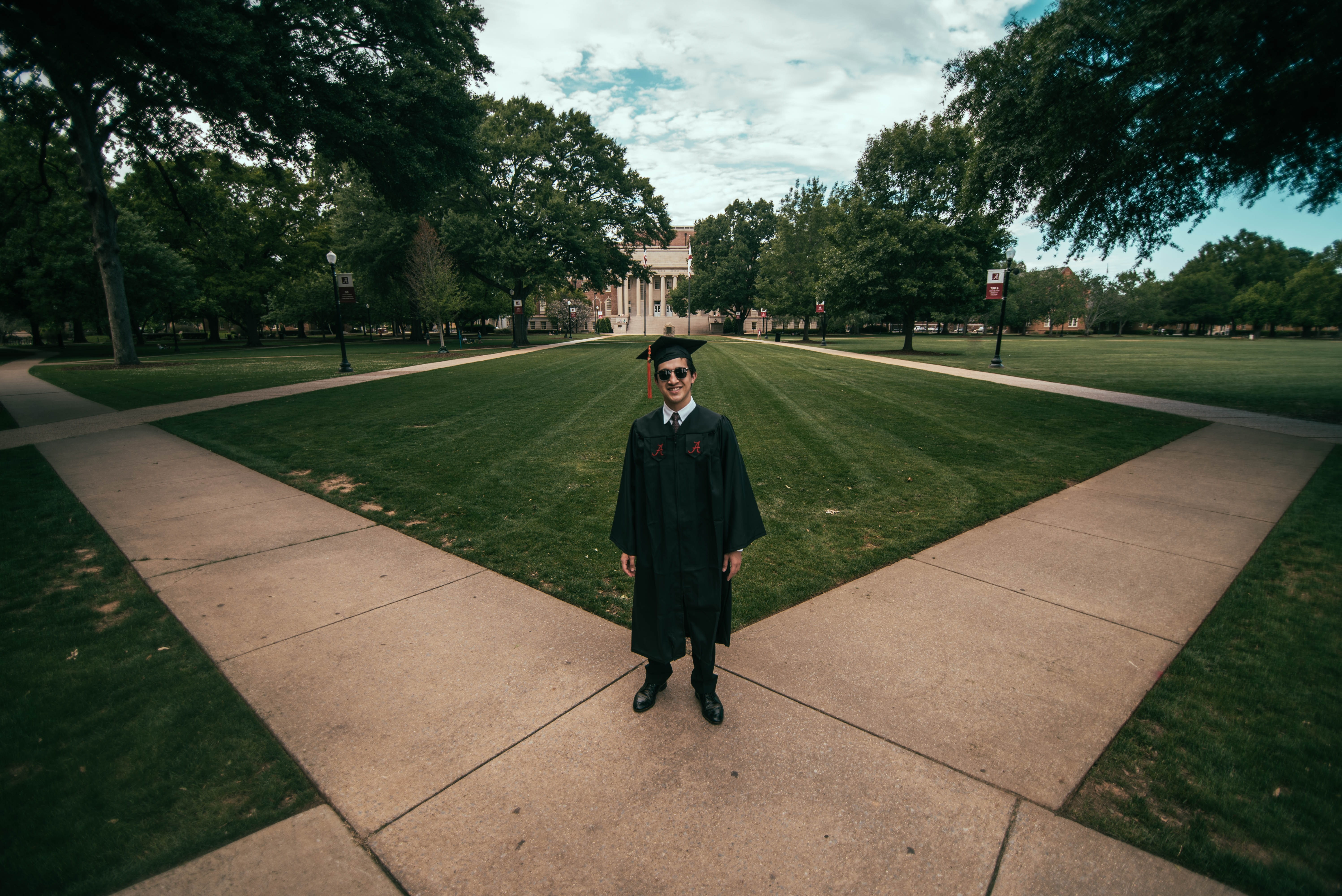man wearing academic gown standing on green field