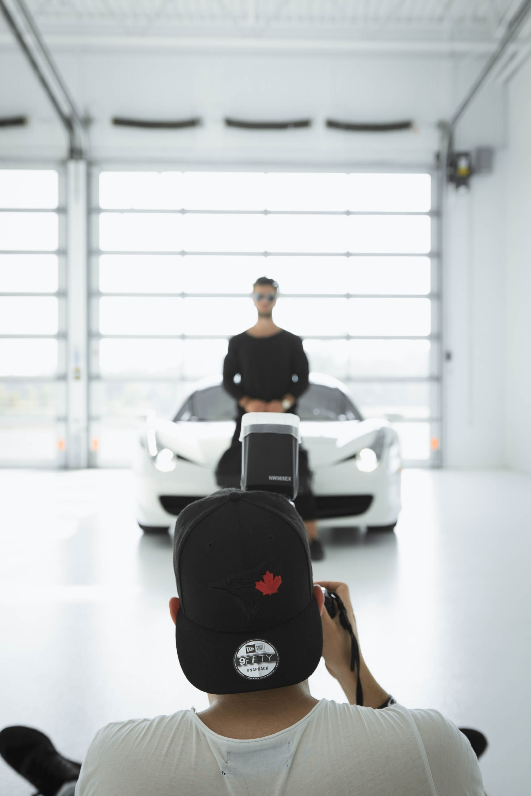 man taking a picture of standing man in front of car inside room