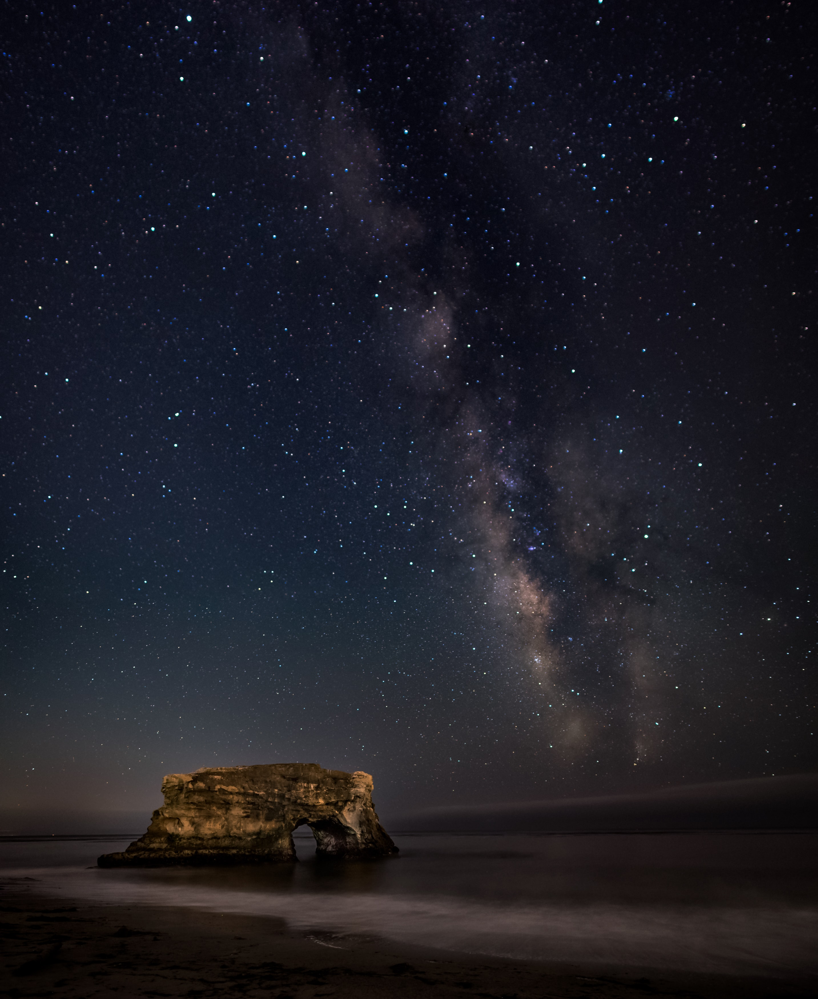 brown rock formation on body of water during nighttime