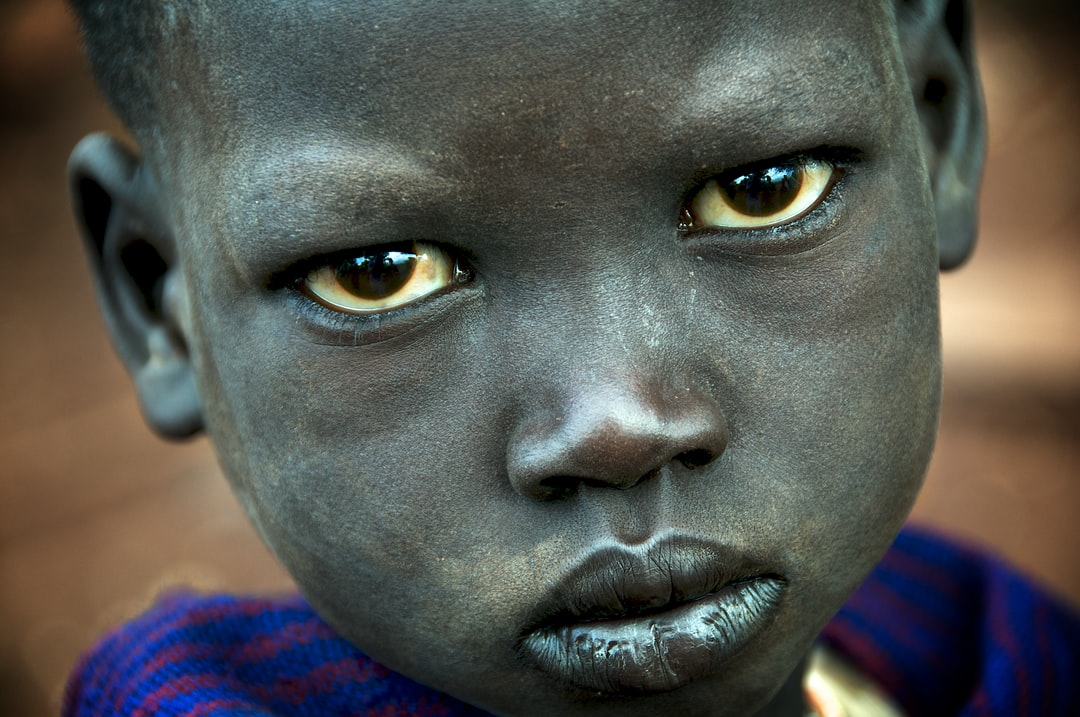 A young boy of the Suri tribe with a pensive look on his face