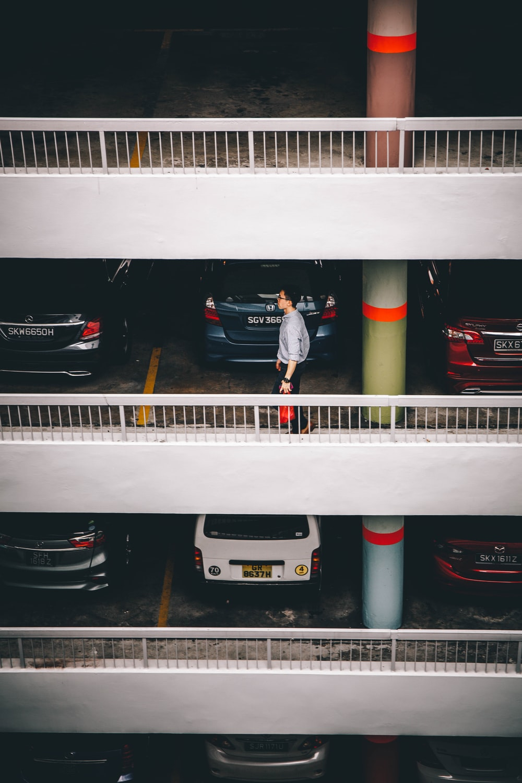 man standing behind vehicles