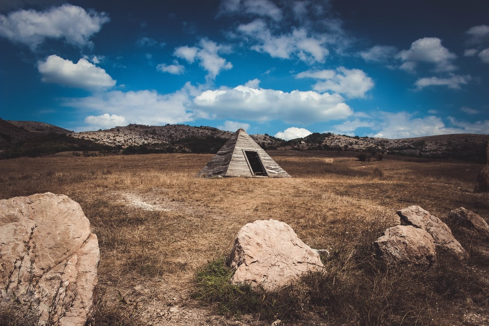 pyramid gray tent on brown field under white clouds