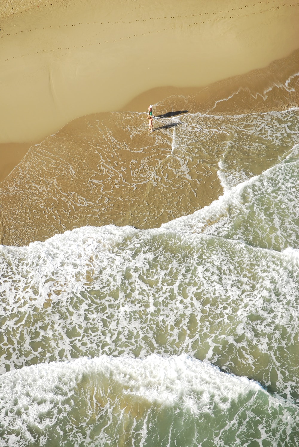 person walking on seashore waves