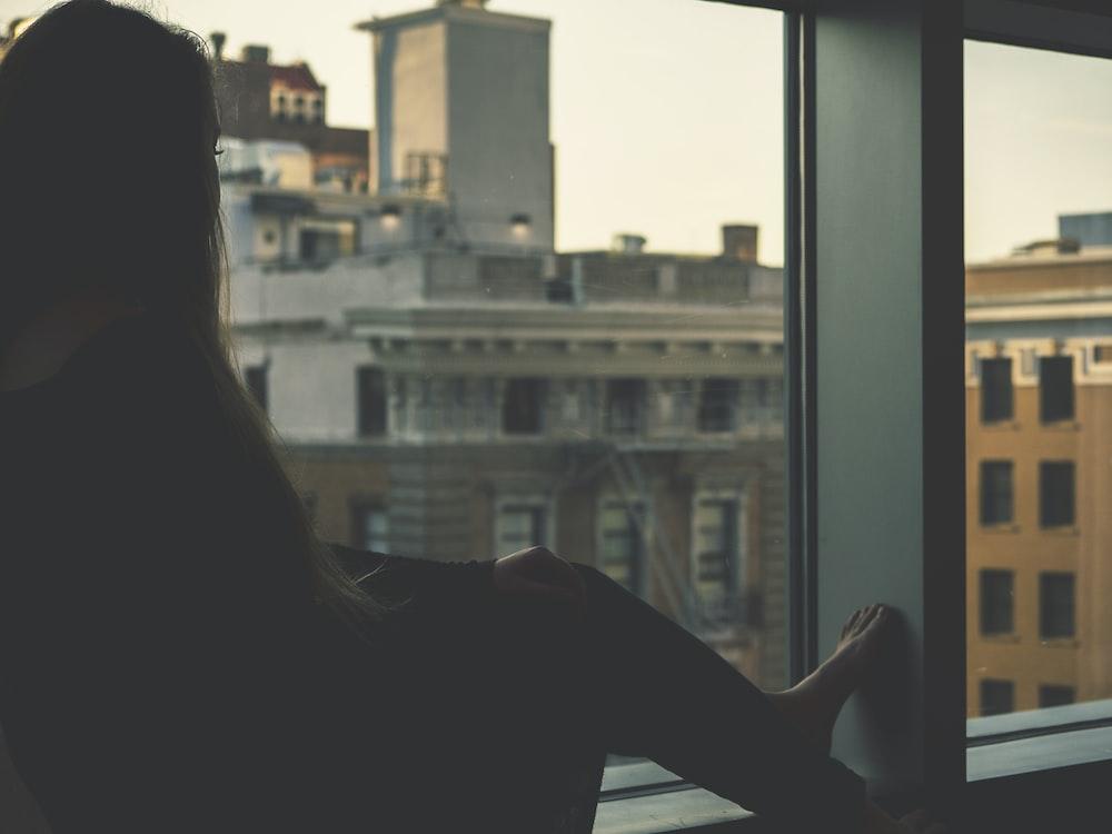 woman in black sitting beside window